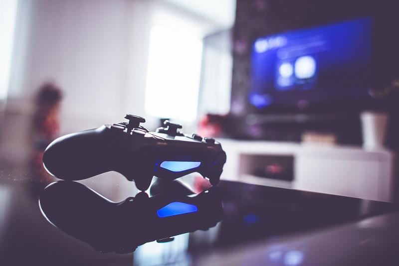 Widok na leżący na powierzchni stolika pad do gier, w głębi widać rozmyty obraz telewizora na tle ściany