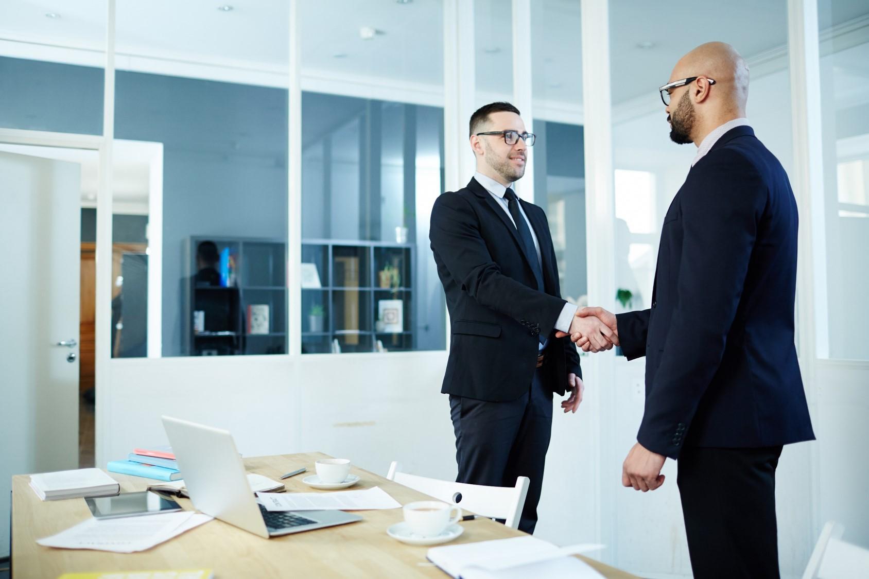 Dwóch mężczyzn w okularach w średnim wieku, ubranych w garnitury stoi obok stołu w sali konferencyjnej i wymienia ze sobą uścisk dłoni.