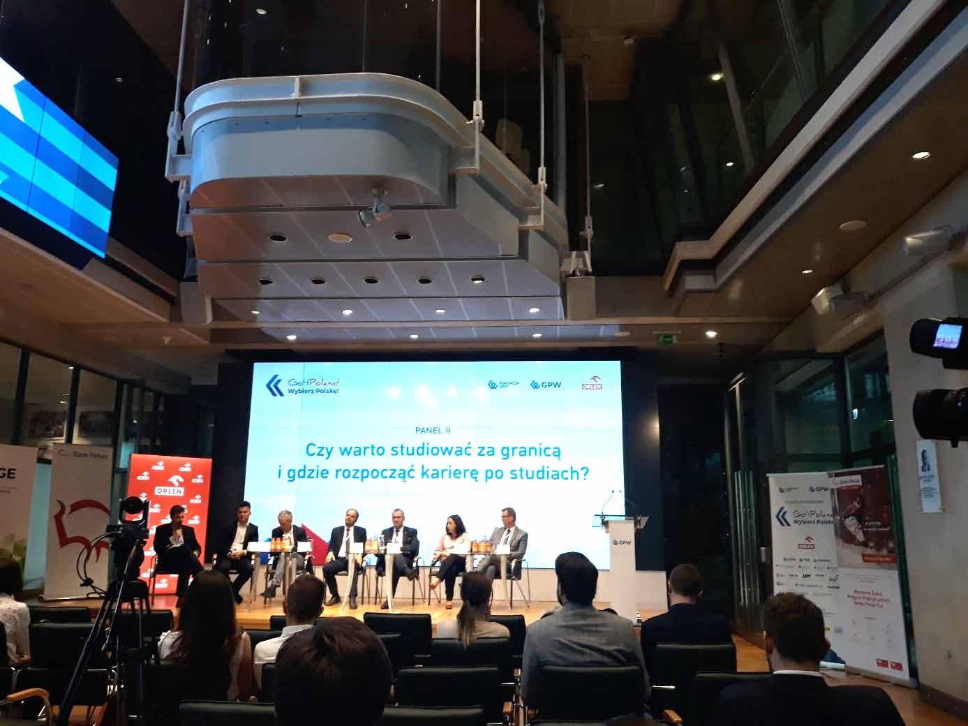 Prelegencji konferencji siedzący na tle ekranu z napisem 'Czy warto studiować za granicą i gdzie rozpocząć karierę po studiach'