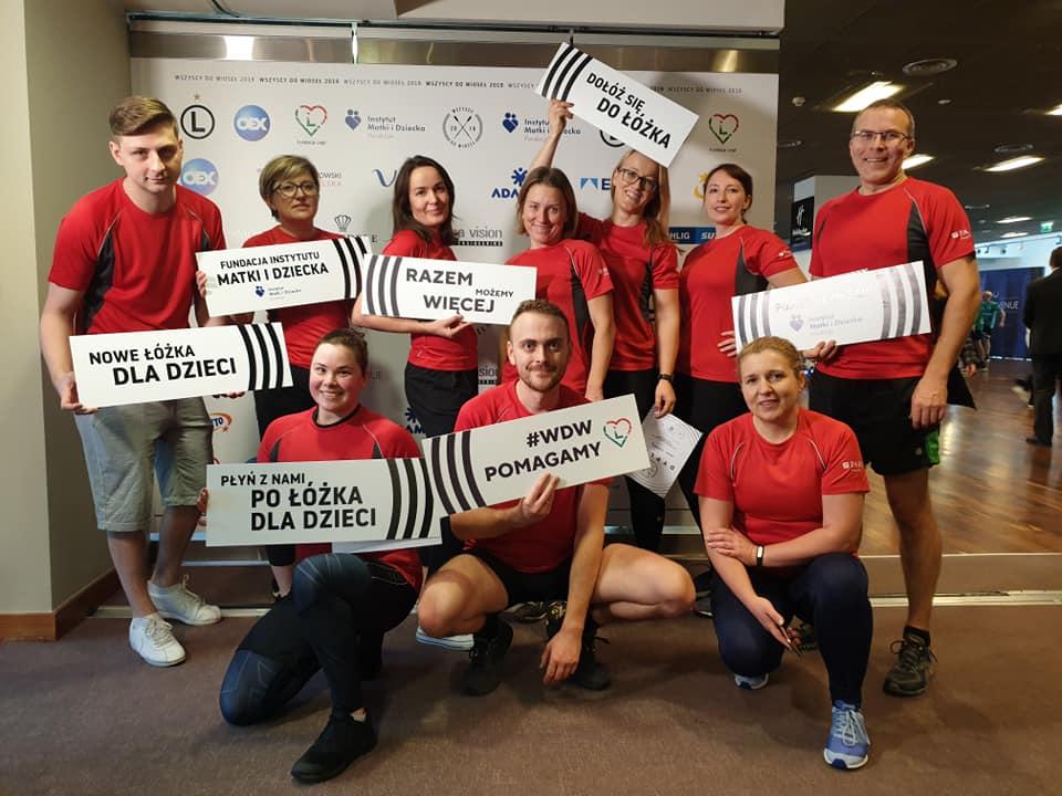 Pracownicy PARP w strojach sportowych trzymający tabliczki z napisami Fundacji Matki i Dziecka - razem możemy więcej